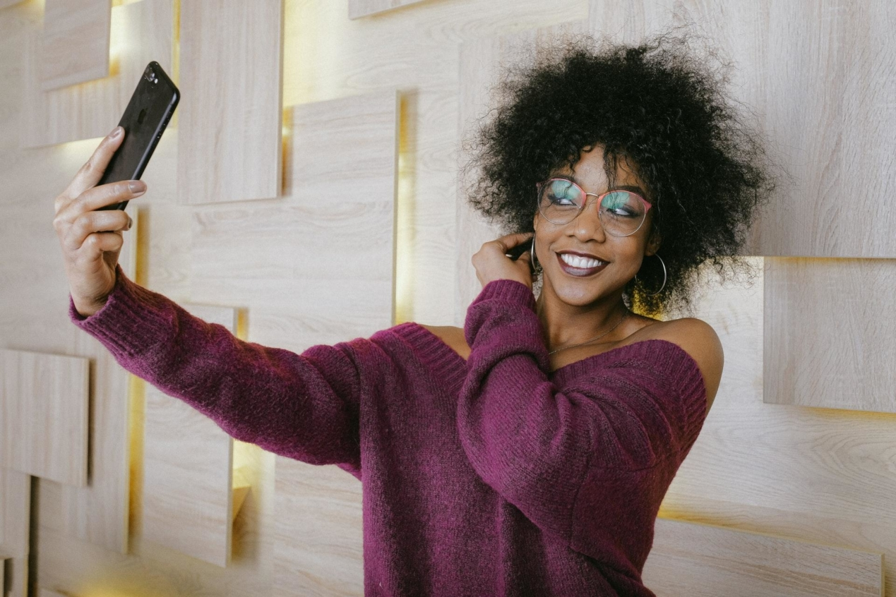 An influencer holding up a phone to take a picture and share it on social media.