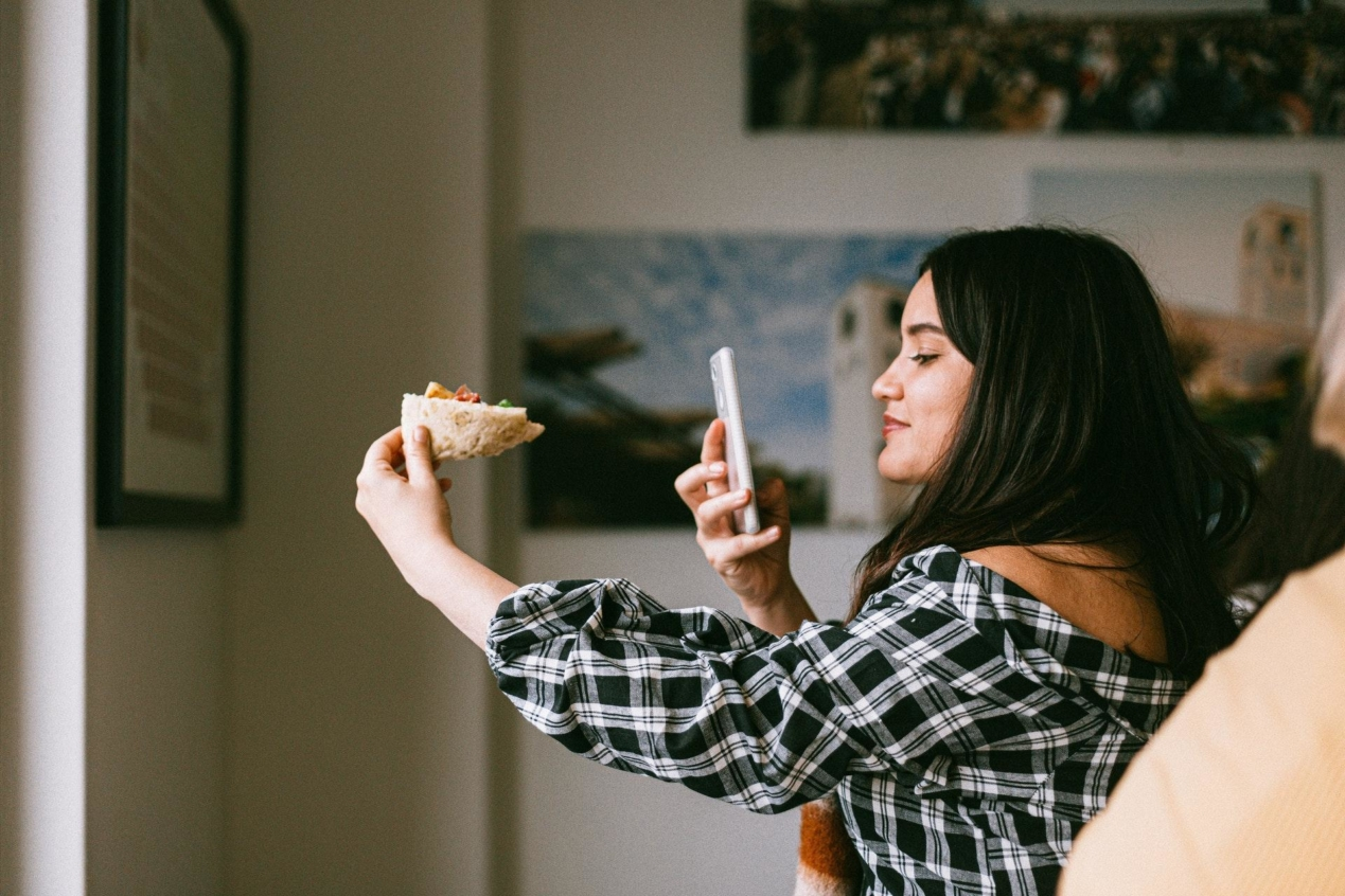 A micro-influencer holding a piece of pizza in front of their phone camera.