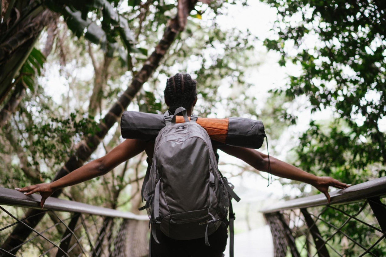 A woman standing on a bridge in a forest with a backpack on.