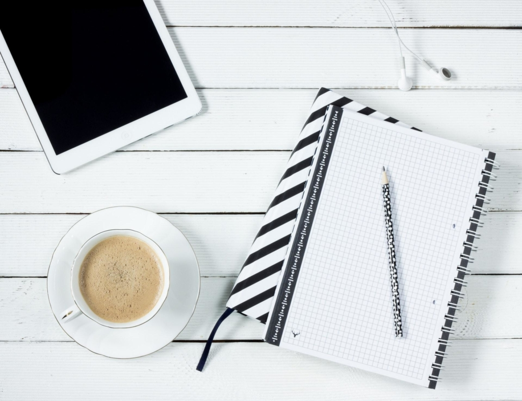 A flat lay photo of a notepad and a cup and saucer on a white background.
