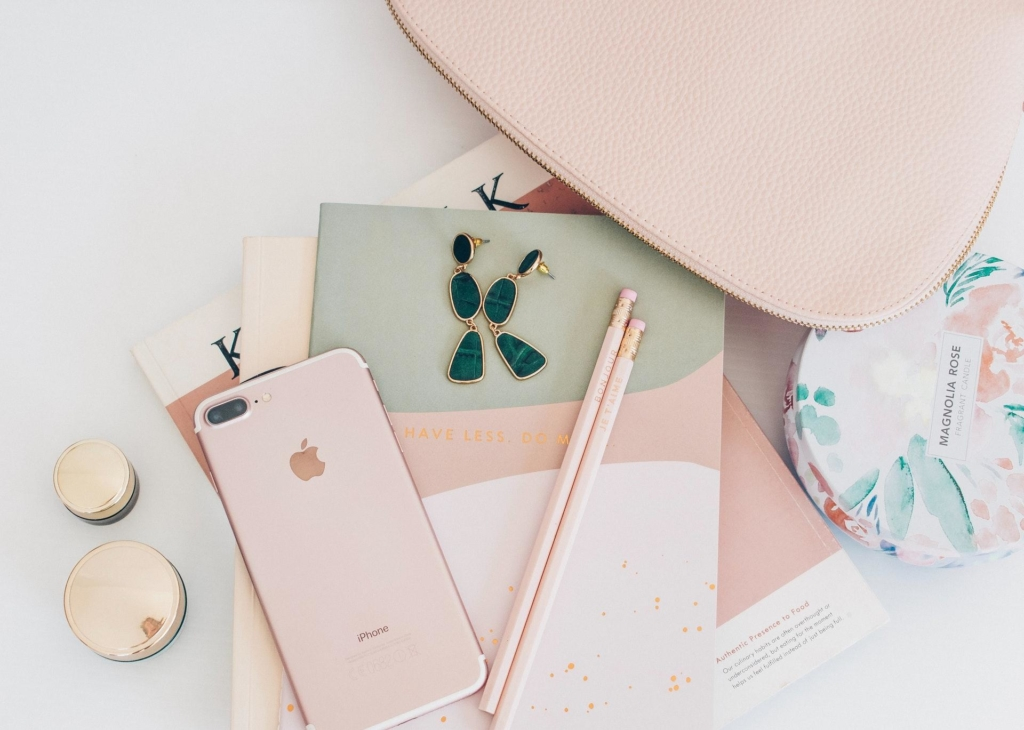 A colour coordinated flat lay photo of a phone, pencils, notepads, earrings, and a candle.